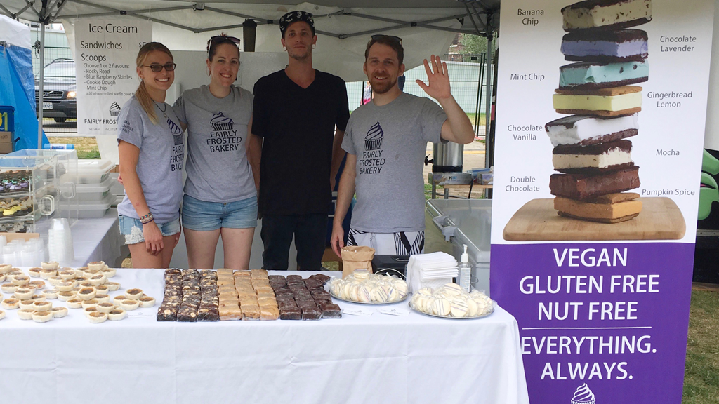 (From left to right) Krisia, Lise, Chris, and Chad (waving) standing behind a table laden with brownies, butterless tarts, and cookies, inside the Fairly Frosted Booth at the 2016 Toronto Vegan Food & Drink Fest.